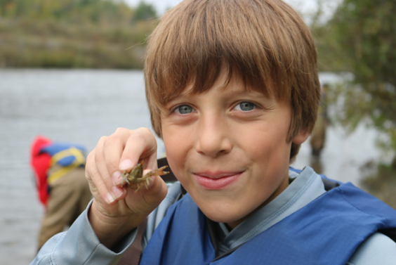 A NEMIGLSI student holds a crayfish up to the camera.  Behind the student a lake and trees can be seen out of focus, along with one person looking into the water.