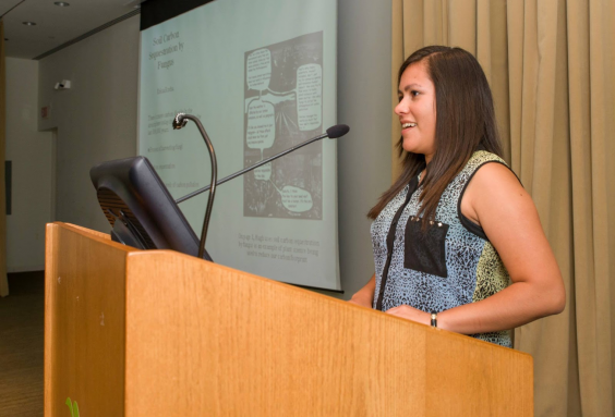 Erica Rocha standing at a podium. Podium and Erica face the left side of the photo, Erica standing on the right side. A powerpoint slide can be seen behind Erica, but the text cannot be made out.
