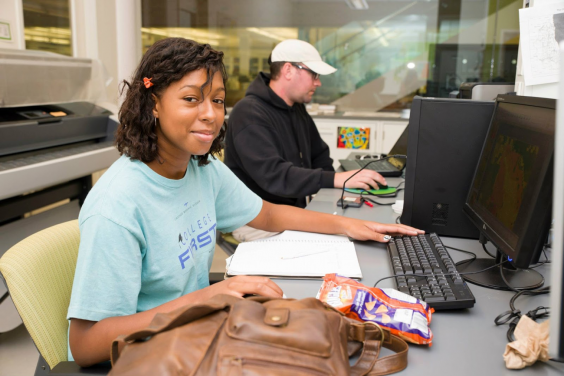 Jannice Newson sitting at a computer. Jannice in on the left in the foreground, facing right and looking towards the photographer. A man in a baseball cap sits at another computer in the background.