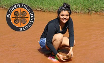 Teenage participant of E4 STEM kneeling in muddy water way with a grassy shore behind her. The Flower Hill Institute Logo brands the top left corner.