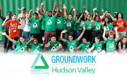 Green Team Greenway Corps members pose as a gropu in front of green cargo container and woods, many of the participants wearing green Groundwork Hudson Valley shirts. Many smiling faces and waving hands. A feathered white backdrop takes up the lower third with the Groundwork Hudson Valley logo over top in blue and green.