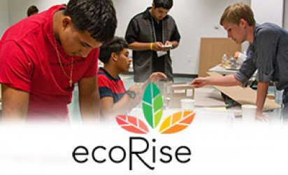 Four students working on models. A boy in a red shirt at the foreground, more prominent than the other three. A white-feathered backdrop covers the lower third with the ecoRise logo at its center: a large R rising at the center of the logo just below three leaves ranging from mutlipe shades of red, to green, to yellow, to orange, in a gradual transition from one leaf to the next over the course of all three leaves. All the leaves radiate out from the dot above the 'i' of Rise.