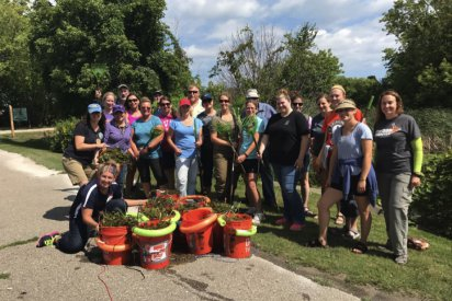 A group of Michigan educators pose curbside on a slope of green grass, with trees, bushes, and other plants in teh background. The educators are smiling, holding rakes, and displaying ten orange buckets full of plant material.
