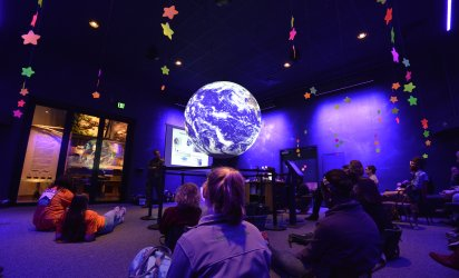 Purples and blues dominate the image. Kids sit in a dim light, lit in purple and blues, as a large globe takes center frame, in front of an adult speaker mid-presentation. Neon stars hang from the cieling.