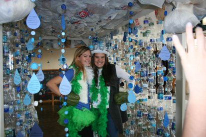 Youth Summit participants pose in an art installation made of recycled plastic bottles, construction paper rain drops, and plastic bags.