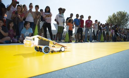 A line of onlookers watch and film as a small solar call shaped to a point races across a yellow track laid out over a blue turf, with triangular flags behind.